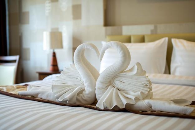 Łabędzie ręczniki na łóżku w pokoju hotelowym