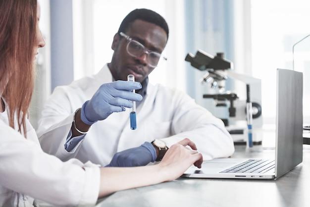 Laboratoria laboratoryjne przeprowadzają doświadczenia w laboratorium chemicznym w przezroczystych kolbach. formuły wyjściowe.