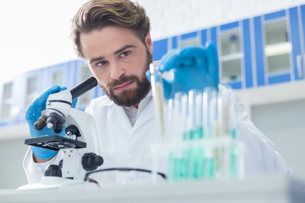 Laboratorium chemiczne. poważny, miły, przystojny naukowiec siedzący przy stole i patrząc na probówkę podczas pracy z próbkami testowymi