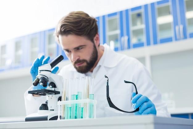 Laboratorium chemiczne. selektywne skupienie się, jeśli probówki stoją na stole z przystojnym profesjonalnym chemikiem pracującym w tle