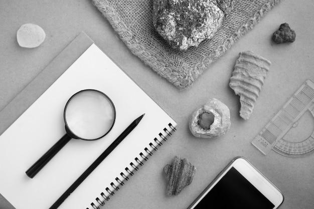 Laboratorium geologiczne skalne. próbki kamieni, pętla, notatnik i telefon komórkowy w laboratorium geologicznym. laboratorium analiz geologicznych materiałów glebowych, kamieni, minerałów, próbek skał dla badaczy