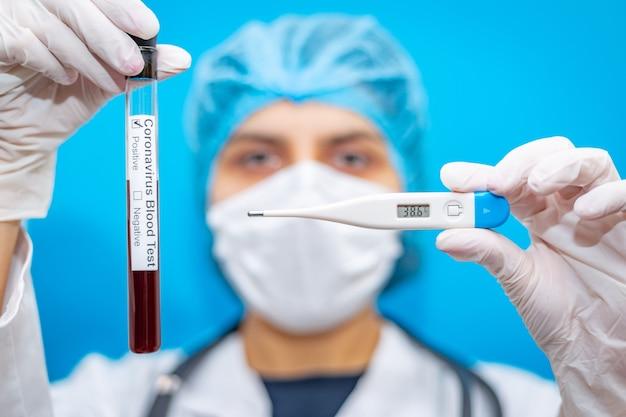 Laboratorium medyczne probówki krwi i termometr wysokiej temperatury w rękach młodej kobiety lekarza wirusolog