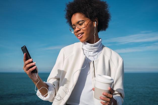 Łacińska kobieta używa telefon komórkowego.