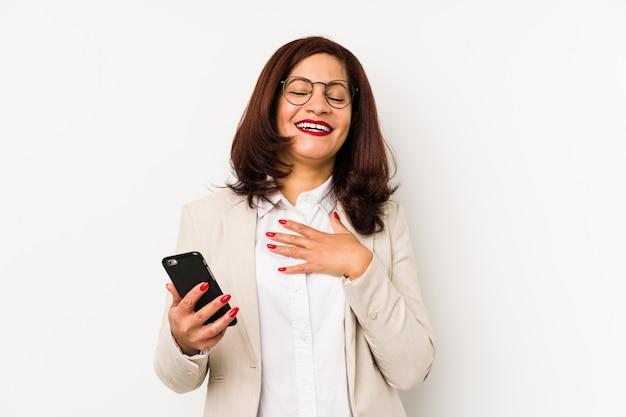 Łacińska kobieta w średnim wieku, trzymając telefon komórkowy na białym tle, głośno się śmieje, trzymając rękę na piersi.