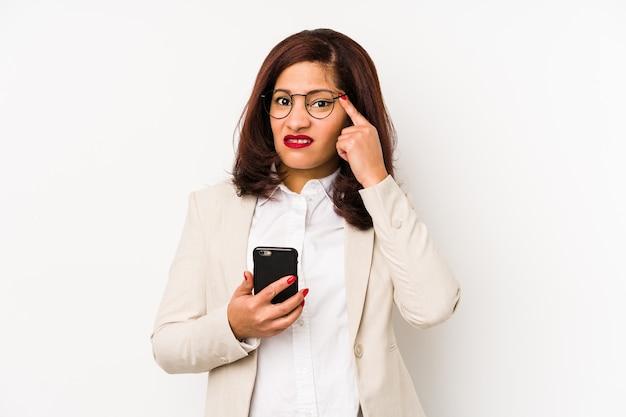 Łacińska kobieta w średnim wieku, trzymając telefon komórkowy na białym tle pokazując gest rozczarowania palcem wskazującym.