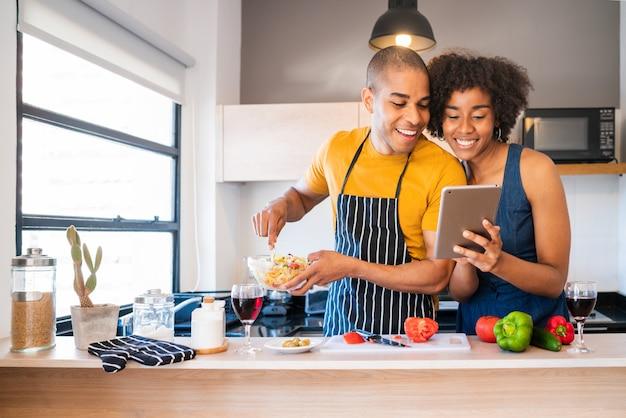 Łacińska para używa cyfrową pastylkę podczas gdy gotujący w kuchni.