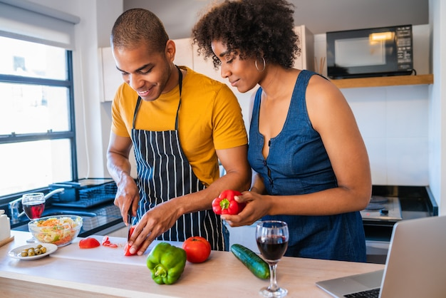Łacińska para używa laptop podczas gdy gotujący w kuchni.