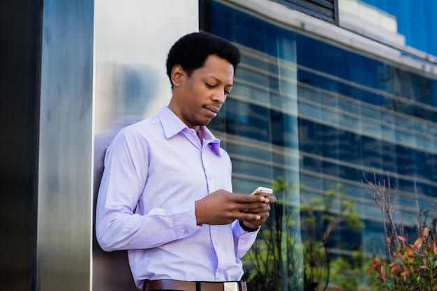 Łaciński biznesmen używa telefon komórkowego w mieście