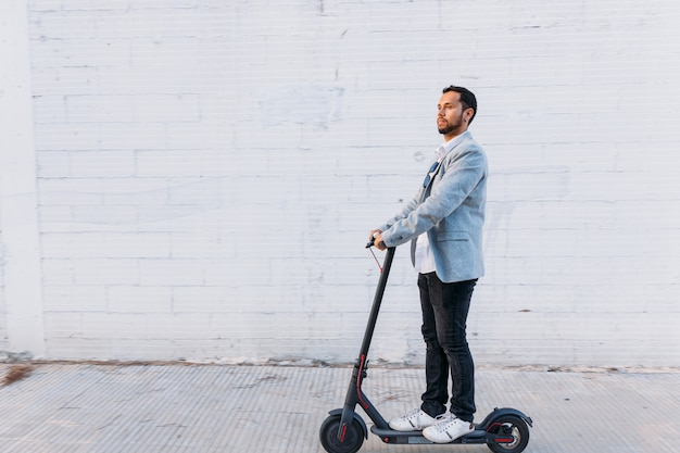 Łaciński dorosły mężczyzna w okularach przeciwsłonecznych, dobrze ubrany i skuter elektryczny na ulicy na tle białej ściany