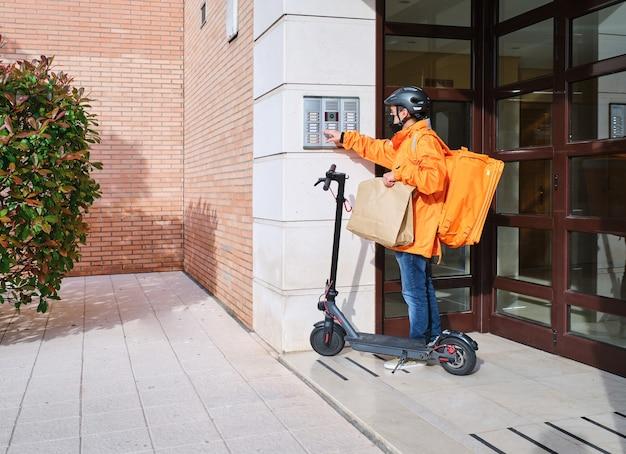 Łaciński dostawca ze skuterem elektrycznym dzwoni dzwonkiem