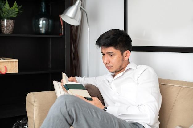 Łaciński mężczyzna czytający książkę na kanapie