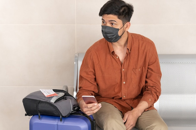 Łaciński mężczyzna siedzący na stacji z walizką i używający telefonu komórkowego
