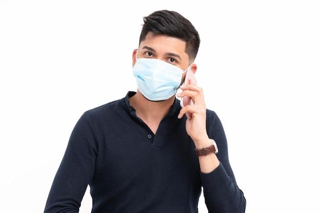 Łaciński mężczyzna siedzący z telefonem komórkowym w ręce z maską