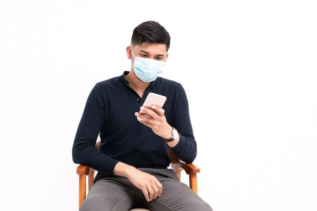 Łaciński mężczyzna siedzi z telefonem komórkowym w ręce z maską