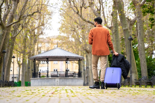 Łaciński Mężczyzna Spacerujący Po Parku Z Walizką Premium Zdjęcia