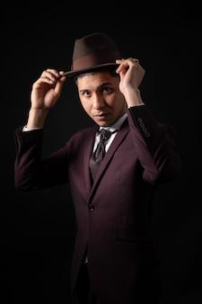 Łaciński mężczyzna w garniturze na czarnym tle z rękami na kapeluszu