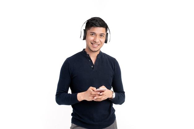 Łaciński mężczyzna z słuchawki i telefon komórkowy, uśmiechając się
