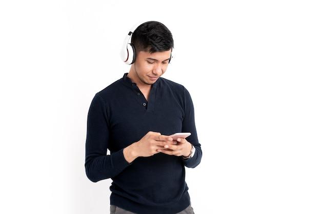 Łaciński mężczyzna ze słuchawkami i telefonem komórkowym