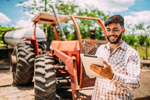 Łaciński wiejski biznesmen sprawdzanie pracy w cyfrowym tablecie.