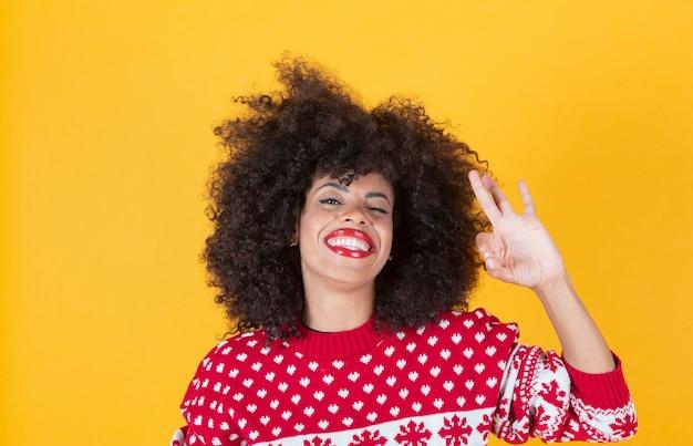 Ładna afro kobieta, ok gest, żółte tło