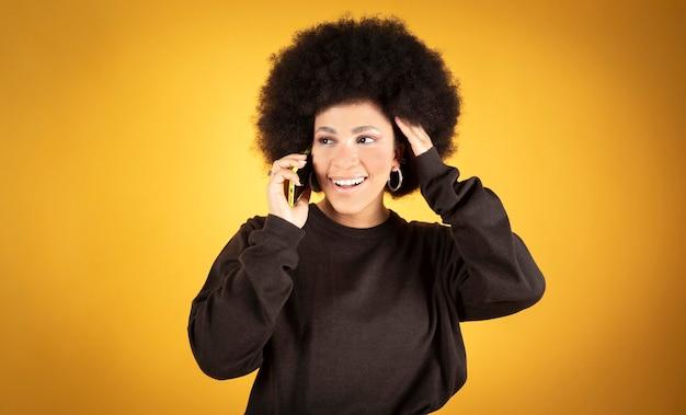 Ładna afro kobieta rozmawiająca na smartfonie