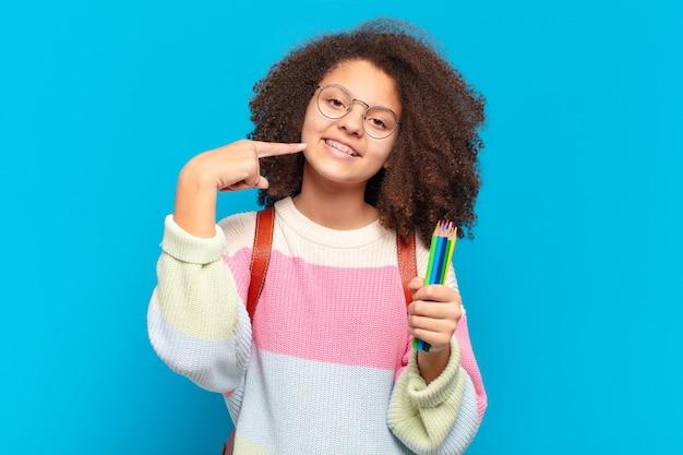 Ładna afro kobieta uśmiechnięta pewnie, wskazując na swój szeroki uśmiech, pozytywne, zrelaksowane, zadowolone nastawienie. koncepcja studenta