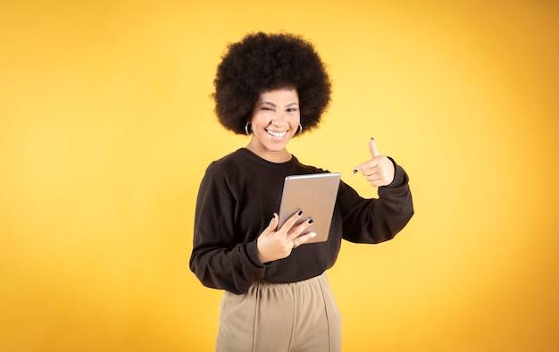 Ładna afro kobieta, uśmiechnięta, wskazująca na swój tablet