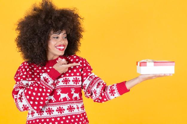 Ładna afro kobieta w świątecznych ubraniach i prezentem w dłoniach, żółte tło