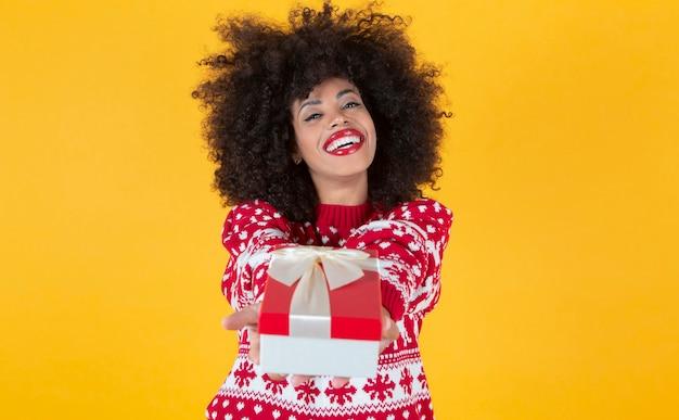 Ładna afro kobieta w świątecznym swetrze z prezentem w dłoniach na żółtym tle