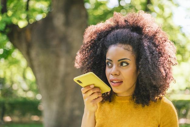Ładna afro kobieta wysyła wiadomość dźwiękową na swój telefon komórkowy. selektywne skupienie.