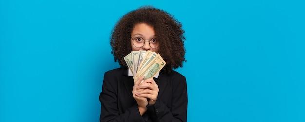 Ładna afro nastolatka biznesowa dziewczyna z banknotami dolarowymi