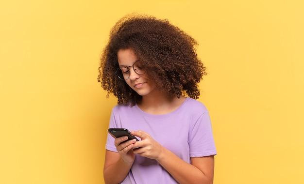 Ładna afro nastolatka używająca komórki
