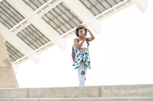 Ładna afro turystka, robiąca zdjęcia swoim aparatem w mieście
