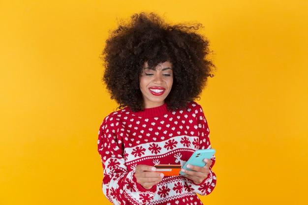 Ładna afroamerykanka, świąteczne zakupy ze smartfonem i kartą kredytową, żółte tło,