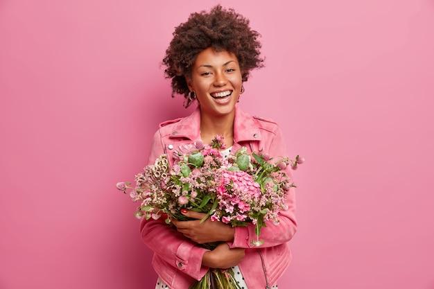 Ładna afroamerykanka wyraża szczere emocje, obejmuje bukiet kwiatów, ma wiosenny nastrój