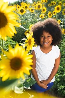 Ładna afroamerykańska dziewczyna w polu słoneczników bawi się