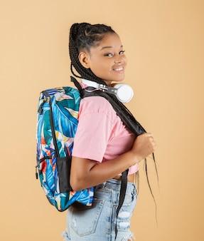 Ładna afroamerykańska dziewczyna z uśmiechniętym plecakiem i słuchawkami