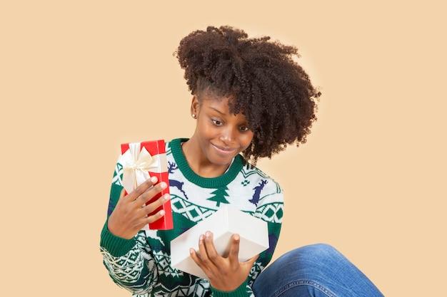 Ładna afroamerykańska kobieta, na boże narodzenie z prezentem, beżowe tło