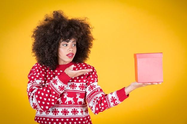 Ładna afroamerykańska kobieta otwierająca świąteczny prezent szczęśliwe żółte tło