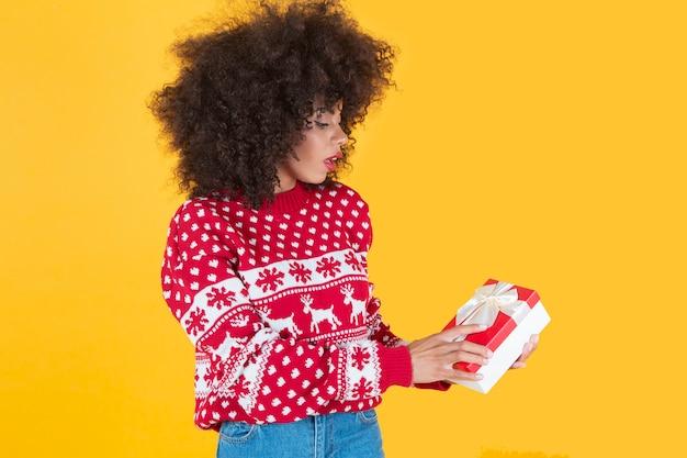 Ładna afroamerykańska kobieta, w boże narodzenie nowy rok, z prezentem w ręku, żółte tło