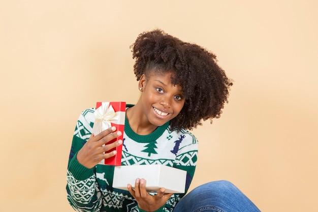 Ładna afroamerykańska kobieta z prezentem świątecznym, beżowe tło