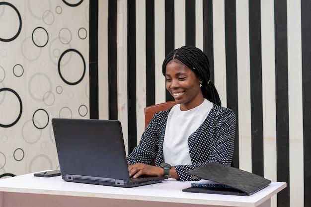 Ładna afrykańska dama czuje się szczęśliwa, gdy pracuje w biurze