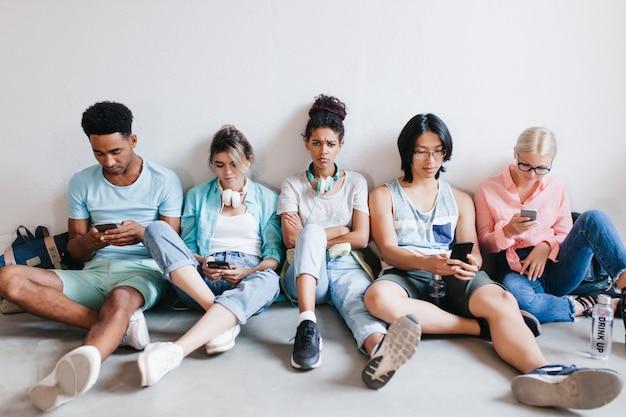 Ładna afrykańska dziewczyna obraża się, ponieważ przyjaciele nie zwracają na nią uwagi podczas korzystania z telefonów. smutne studentki z kręconymi włosami siedzą między kolegami z uniwersytetu z założonymi rękami.