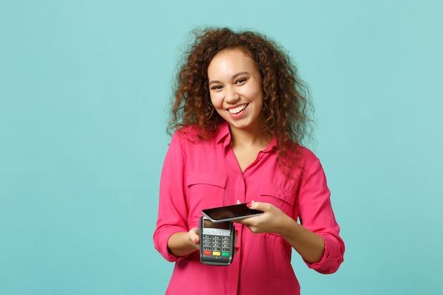 Ładna afrykańska dziewczyna trzymać telefon komórkowy bezprzewodowy nowoczesny bankowy terminal płatniczy do przetwarzania nabyć płatności kartą kredytową na białym tle na niebieskim tle turkus. koncepcja życia ludzi. makieta miejsca na kopię.