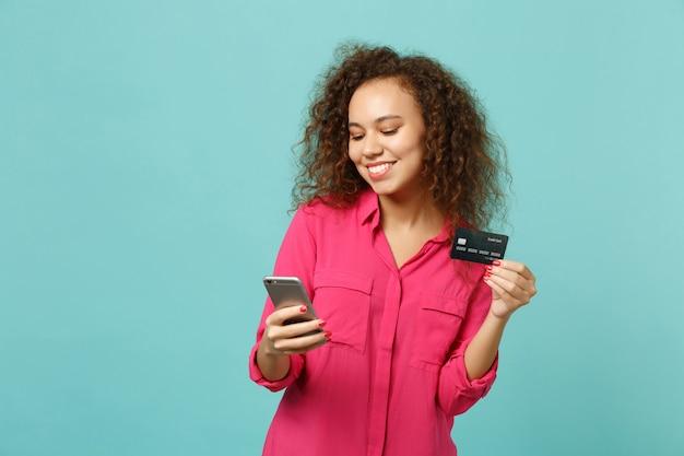Ładna afrykańska dziewczyna w różowe ubrania dorywczo za pomocą telefonu komórkowego, trzymając kartę kredytową bankową na białym tle na niebieskim tle turkusowym w studio. koncepcja życia szczere emocje ludzi. makieta miejsca na kopię.