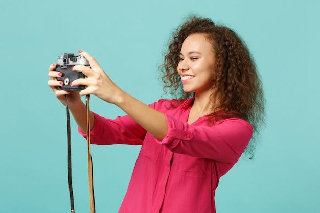 Ładna afrykańska dziewczyna w ubranie robi selfie strzał na retro vintage zdjęcie aparatu na białym tle na niebieskim tle turkusu w studio. koncepcja życia szczere emocje ludzi. makieta miejsca na kopię.