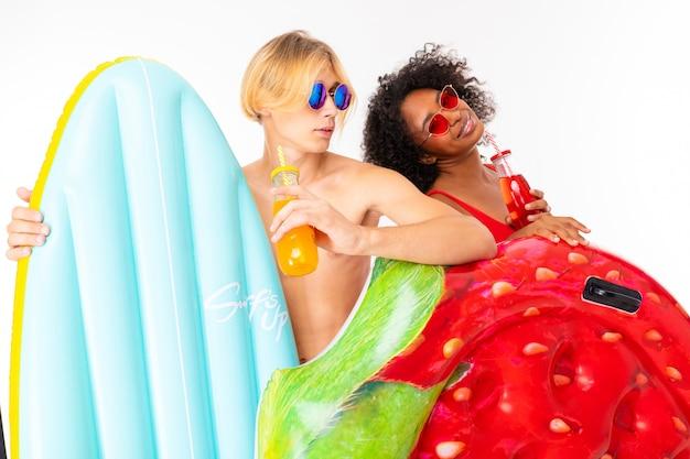 Ładna afrykańska kobieta i caucasian blondynka mężczyzna stoi w swimsuit z gumowymi plażowymi materacami i uśmiechami odizolowywającymi na białym tle