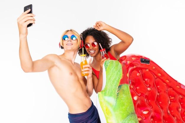 Ładna afrykańska kobieta i caucasian blondynka mężczyzna stoi w swimsuit z gumowymi plażowymi materacami, pije sok i robi selfie wpólnie odizolowywającemu na białym tle