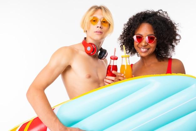 Ładna afrykańska kobieta i caucasian caucasian mężczyzna stoi w swimsuit z gumowymi materacami plażowymi, pije sok i ono uśmiecha się, odizolowywającymi na biel ścianie