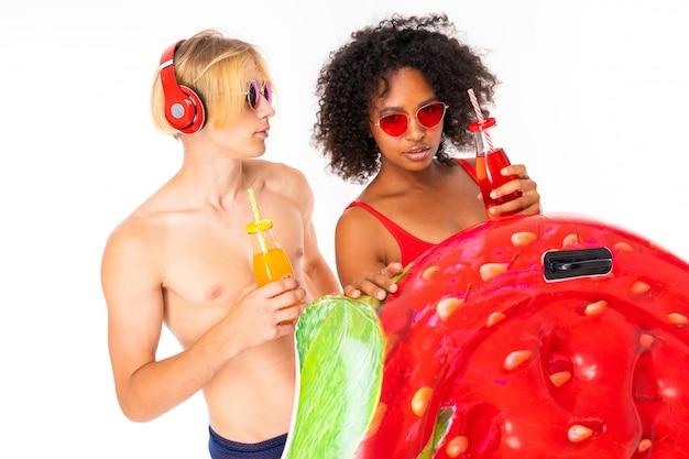 Ładna afrykańska kobieta i caucasian caucasian mężczyzna stoi w swimsuit z gumowymi materacami plażowymi, pije sok i słucha muzyki odizolowywającej na biel ścianie